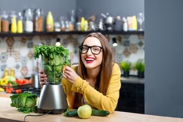 Portrait of young smiling woman with blender full of fresh greens, kiwi and gabbage ready to mix in the kitchen at home. Healthy vegetarian smoothie for weight loss and detox