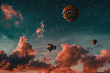 Hot air balloon in the sky at the sunset with red clouds.