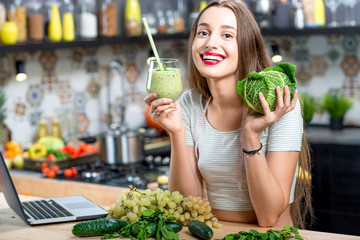 Portrait of young smiling woman with green smoothie in the kitchen at home. Healthy vegetarian diet for weight loss and detox