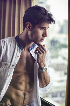 Sexy young man standing with shirt open on muscular chest in his bedroom next to window curtains