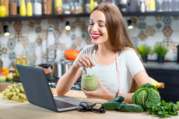Young woman sitting on the kitchen table with laptop, smoothie and green vegetables. Healthy eating, weight loss and detox concept