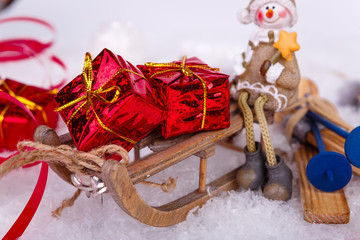 Xmas or new year composition with holiday decorations - little toy sledge with gifts boxes and little toy man. Christmas card