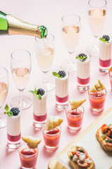 Various snacks, brushettas, gazpacho shots, desserts with berries and champagne pouring to glasses on corporate event, christmas, wedding celebration over pastel pink background, selective focus