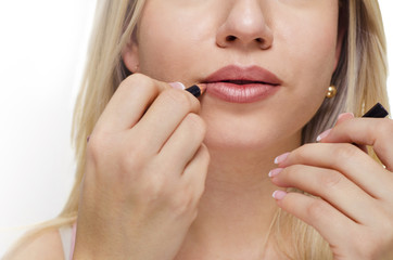 Closeup of blonde young woman putting lipstick