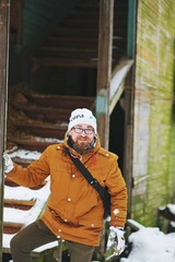 Young bearded smiling man with the bag behind posing near an old abandoned house during a country walk in winter.