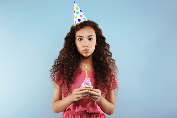Beautiful African girl with birthday cake on color background
