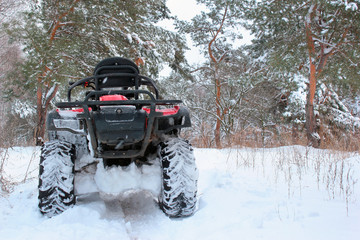 Snow covered quad bike in winter forest