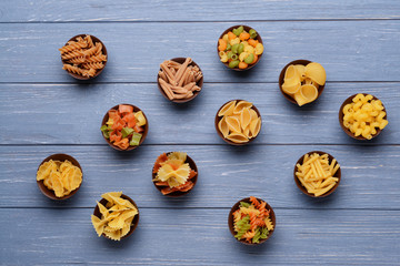 Different kinds of pasta in bowls on wooden background