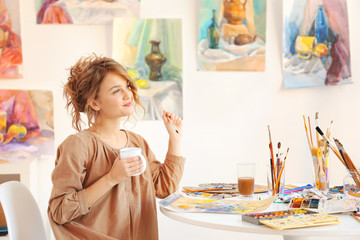 Young female artist drinking coffee in studio