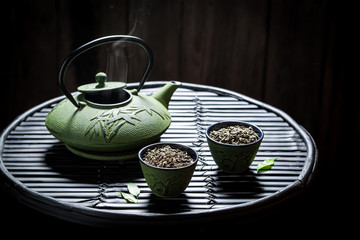 Fresh green tea with teapot on black table