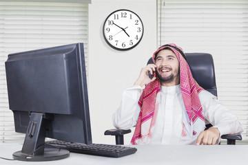 Arabian man smiles with smartphone
