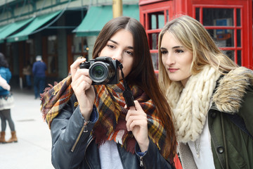 Two young tourists taking a photo with camera.