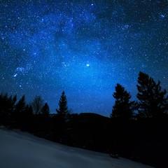 Milky Way in sky full of stars. Winter mountain landscape in night.