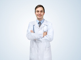 Young doctor on light background