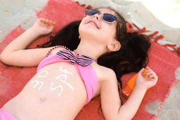Cute little girl with sun block cream at beach