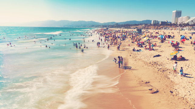 People visit the beach in Santa Monica, CA
