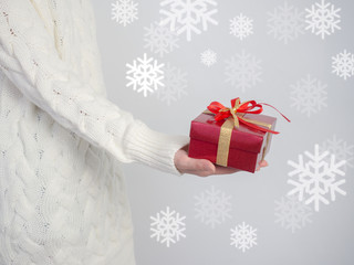 Celebrate year 2017.Close up shot of female hands holding a gift box and nice ribbon. Gift box color  in the hands of a woman wearing a knitted hat sweater on white snow , snowflake background.