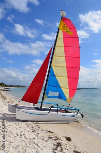 Small Sailing Catamaran Available For Rent Resting In The Sand At A