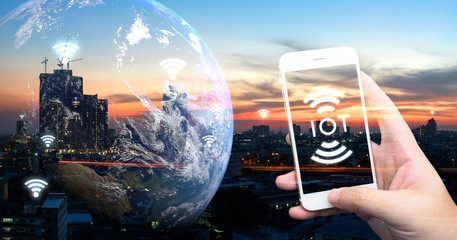 Internet of things , iot , smart home , smart city and network connect concept. Human hand holding white phone and iot icon with city sunset view and earth furnished by NASA. background and wifi icons Fotoväggar