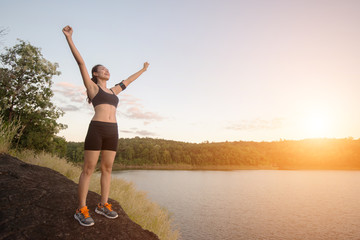 Young fitness woman achieve hiking on peak with lake view sunset