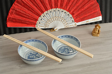 Chines bowls, chopsticks, a hand fan and a laughing Buddha
