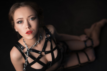 BDSM. Studio photo of beautiful girl on leash