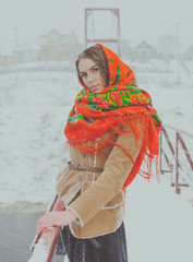 beautiful girl in a scarf in the winter stands on the bridge holding onto the railing.