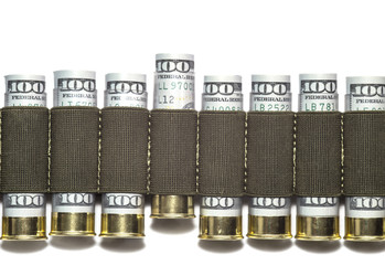 Row of 12 caliber shotgun shells loaded with hundred us dollar bills in bandolier.  One shell is moved upward. The concept of the power of money. Isolated on white background.