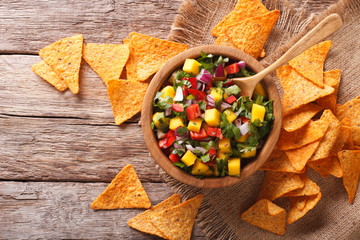 Delicious salsa with mango, chilli pepper, cilantro and onion in a bowl and nachos. Horizontal top view