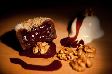 Chocolate Fondant cake with nuts and ball of ice cream on wooden board