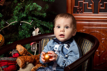 Christmas baby, amazed child boy with christmas ball in hand waiting christmas gifts near christmas tree at home