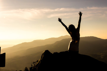 The silhouette of a woman in a yoga pose on the mountain at the Sunset.