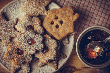 Homemade Christmas gingerbread and linzer cookies with jam, powdered, top flat view, soft haze effect, vintage