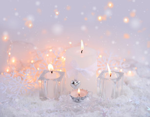 Christmas candles on the snow and Christmas lights. Festive Christmas background