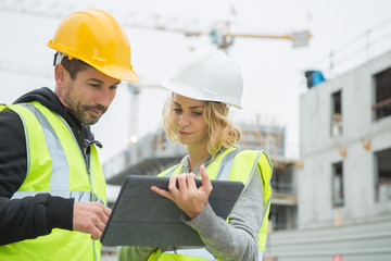 builders in hardhat with tablet at construction