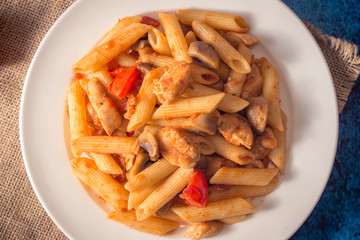 Penne pasta with mushrooms, chicken, tomatoes and cheese parmesa