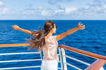 Cruise ship vacation woman enjoying travel vacation having fun at sea. Free carefree happy girl looking at ocean with open arms in freedom pose.