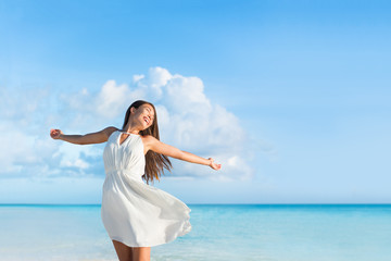 Wall Mural - Freedom young woman with arms up outstretched to the sky with blue ocean landscape beach background copy space. Asian girl in white dress dancing carefree in sunset.