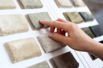 Sklep z dywanami. Kobieta w sklepie z dywanami wybiera dywan z próbnika