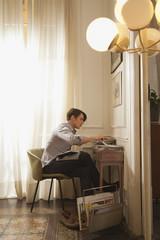 Man reading at desk at home
