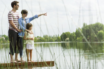 Family standing on dock looking into distance