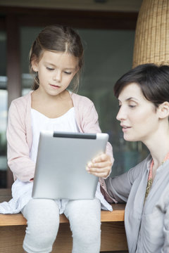 Mother and young daughter using digital tablet