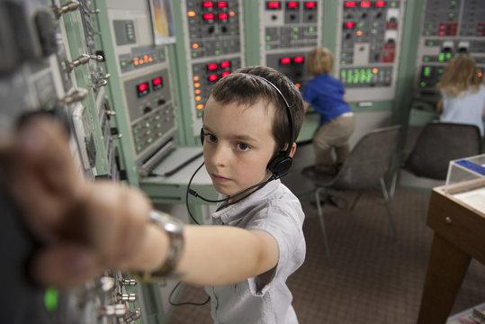 Boy enjoying interactive exhibit at space museum