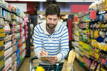 Man writing on notepad while shopping in grocery section