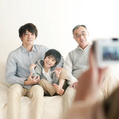 ソファーに座り記念写真を撮る家族