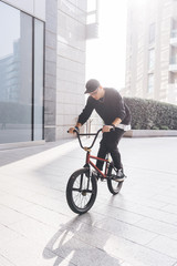 Young man riding BMX bike in city