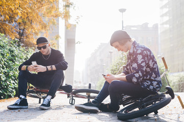 Two young guys using smart phone
