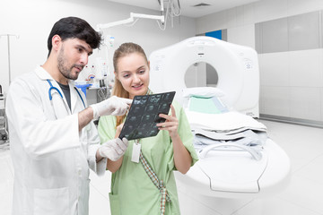 Doctor in CT scan room examining an x-ray and discussing with patient