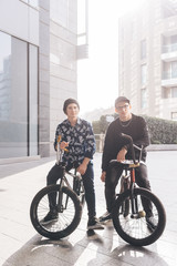Portrait of young men sitting on BMX bikes outdoors