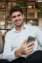 Businessman sitting in cafe and chatting by phone